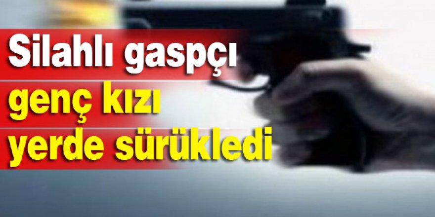 Silahlı gaspçı genç kızı yerde sürükledi