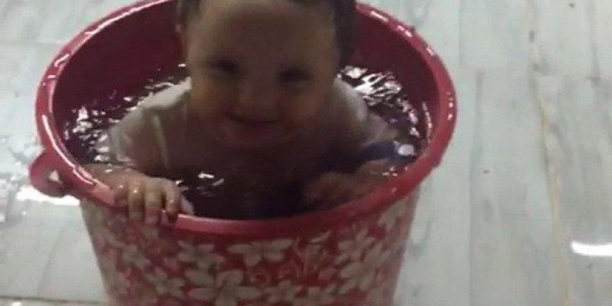 Sıcaktan bunalan bebek su dolu kovada serinledi